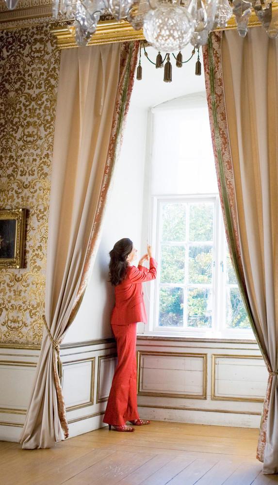 Alexandra von Schwerin öppnar fönstren i vita salongen, en av utställningens salar. Foto: Håkan Sandbring.